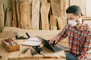 General Contractor in Woodworking Shop Looking at Laptop
